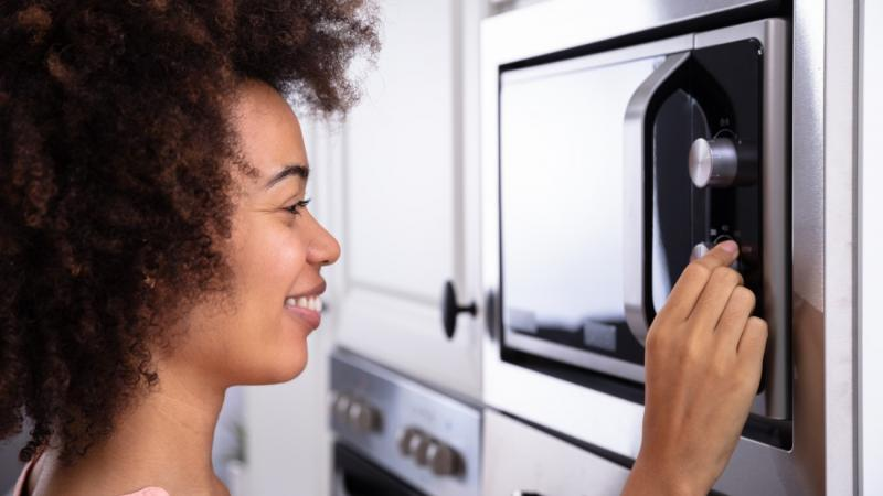 woman typing on microwave buttons