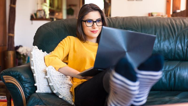 woman lounging on couch with laptop